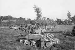 British_infantry_and_Sherman_tanks_wait_to_advance_at_the_start_of_Operation_Goodwood_Normandy_18_July_1944._B7513